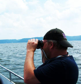 Todd Roll uses binoculars to search for Pepie the Lake Monster
